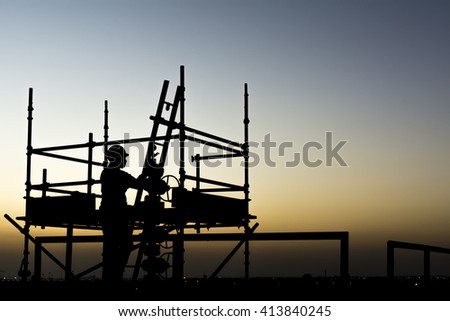 Sunset - Silhouette of oilfield worker on a scaffold working on wellhead - oilfield  - stock photo