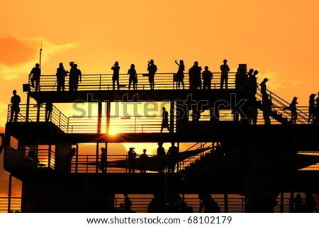 Sunset silhouette of peoples at view point. - stock photo