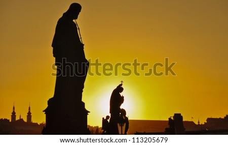 Sunset Silhouette of sculptures on Charles Bridge. Prague, Czech Republic - stock photo