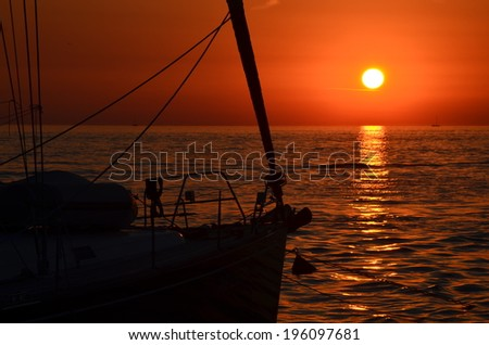 sunset silhouette of the ship's bow and the wavy sea surface / Sunset at Sea