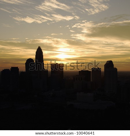 Sunset silhouetting aerial view of Charlotte, North Carolina city skyline.