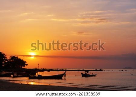 Sunset sky and fishing boats on beach at Lanta island, Krabi, Thailand. - stock photo