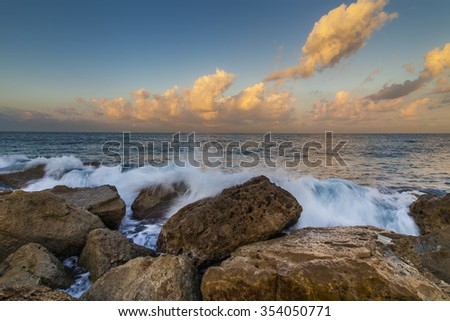 Sunset sky over the waves of the sea. - stock photo