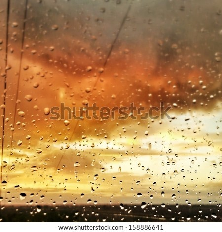 sunset sky with clouds seen through raindrops on glass - stock photo