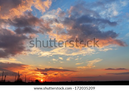 Sunset sky with dramatic clouds and red sun - stock photo