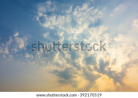 sunset sky with rays of light shining down pass clouds and sky - stock photo