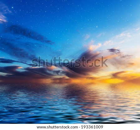 Sunset sky with stars reflected in water surface.  - stock photo