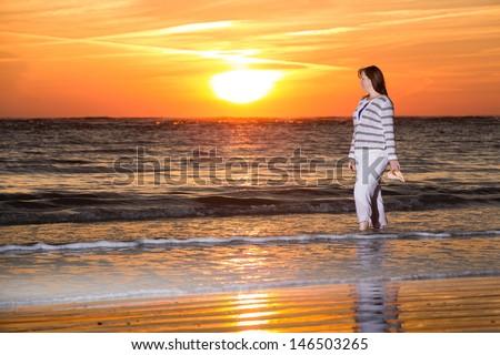 Sunset Stroll on the Beach - stock photo