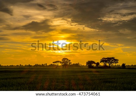 Sunset / sunrise with clouds, light rays on field at countryside Thailand