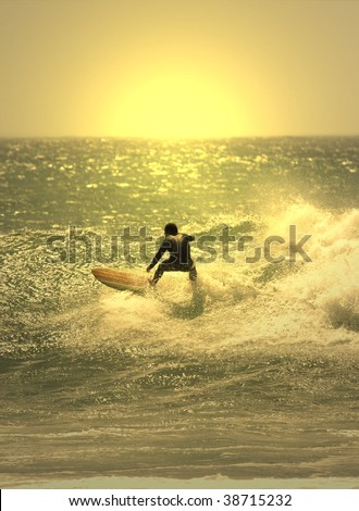 sunset surfer in the wave - stock photo