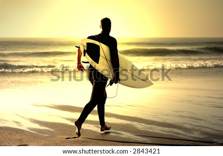 sunset surfer running in the beach - stock photo