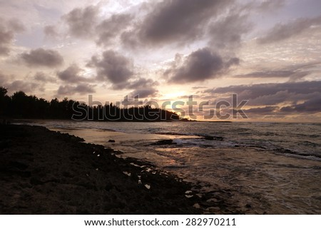 Sunset through the clouds and over the trees as it reflects on the watery waves at Kawela Bay rocky shore on the North Shore of Oahu. - stock photo