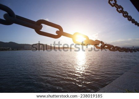 sunset through the iron chain hole over the sea - stock photo
