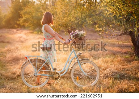 Sunset time. Young women with bicycle in the meadow