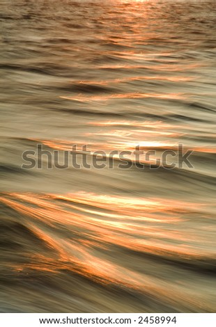 Sunset topped waves purposely photographed to capture the motion blur from aboard a moving boat.