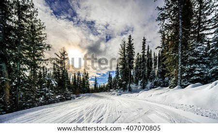 Sunset under a partly cloudy sky over the forest on the ski hills at the village of Sun Peaks in the Shuswap Highlands of British Columbia, Canada - stock photo