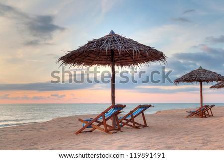 Sunset under parasols on the beach, Thailand - stock photo