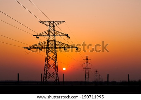sunset under the high-voltage tower in the background - stock photo