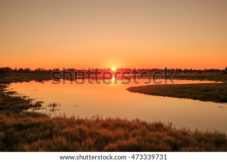 sunset view of a beach naturally forming a beautiful lakes filled with sea water