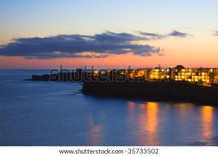 Sunset view of a beach with reflexes in the sea of Lanzarote island - stock photo