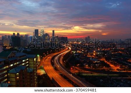 Sunset view of Kuala Lumpur Skyline overlooking Ampangâ??Kuala Lumpur Elevated Highway (AKLEH) and Kampung Datuk Keramat, Malaysia - stock photo