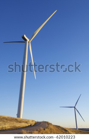 sunset view of modern windmills on a hill - stock photo
