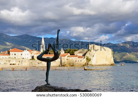 Sunset view of old town Budva: Dancing girl against ancient walls and red tiled roof. Montenegro, Europe.