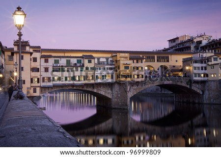 Sunset view of ponte vecchio with reflection on the arno river - stock photo