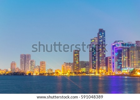 Sunset view of the Khalid lagoon surrounded with skyscraper in the emirate Sharjah, UAE