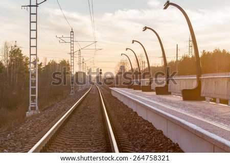 Sunset view on railway track at a small railroad station - stock photo