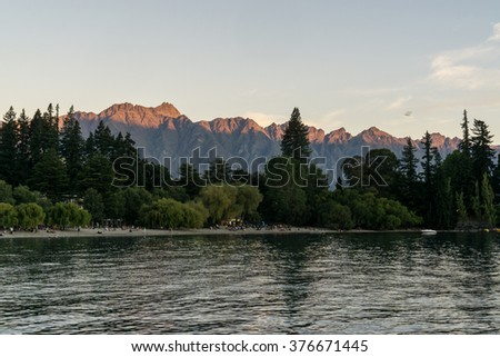 sunset view over remarkables in queenstown over lake wakatipu. Taken during summer in New Zealand. - stock photo