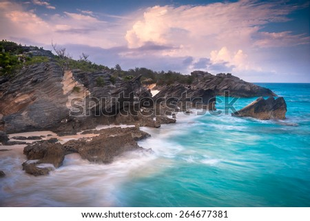 Sunset view over the Horseshoe Bay beach on Bermuda island with beautiful turquoise waves hitting the shore - stock photo