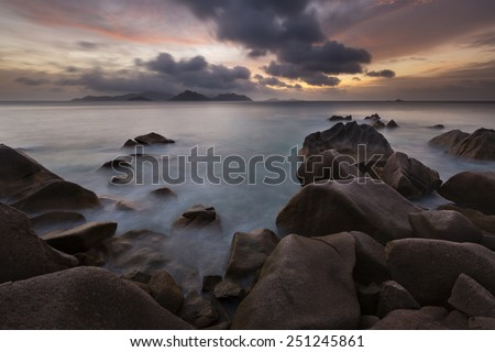 Sunset view to Praslin from La Digue, Seychelles with granite rocks in the foreground - stock photo
