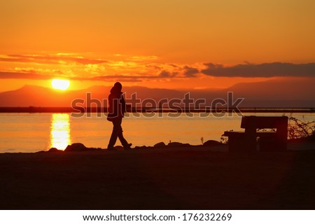 Sunset Walk, Richmond, British Columbia. A walk along the Fraser River at sunset in Richmond, British Columbia. The mountains of Vancouver Island are visible in the background.  - stock photo