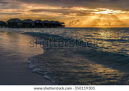 Sunset. Water bungalows at sunset. - stock photo