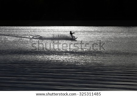 Sunset waterskiing wakeboarder silhouette sprays wate - stock photo