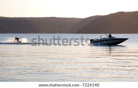 sunset waterskiing wakeboarder sprays water behind fast speed boat in pittwater, sydney, NSW, australia
