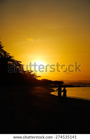 Sunset  while a couple walk on beach . - stock photo