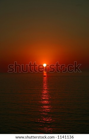 Sunset with boat in reflection - stock photo