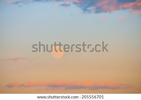 Sunset with colorful moon and clouds on a hazy sky - stock photo