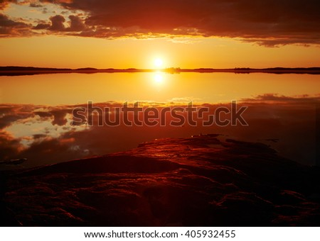 Sunset with crimson red color in the clouds and the rocks on the shore. Dramatic reflection of the Sun in the still water of a lake in Finland. - stock photo
