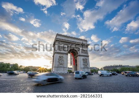 Sunset with dramatic sky behind Arc de Triomphe and blurred cars traffic along the Champs-Elysees  - stock photo
