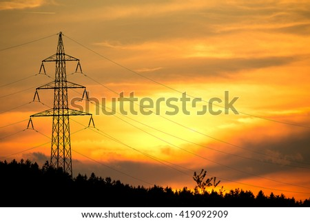 sunset with electricity tower in countryside. Spring scene. Dusk sky with sun. Spring sunset