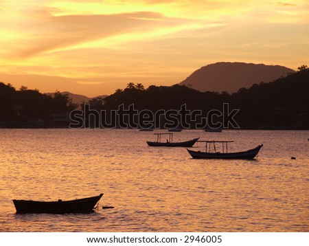 Sunset with fisherboats in the foreground in the bay of Porto Belo - Brazil.
