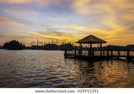 Sunset with low light long exposure scenery of a lake with wooden observation jetty in blue hour, with motion blur effects on surface of water and sky. - stock photo