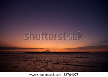 Sunset with moon over the ocean - stock photo