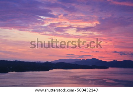 Sunset with ocean, island and sky with clouds in purple and pink.