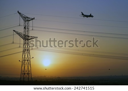 Sunset with pylon and airplane                                - stock photo