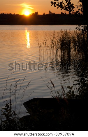 Sunset with silhouette of boat and grass. Focus on foreground - stock photo