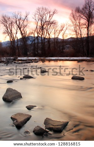 Sunset with silhouetted trees above the Provo River, Utah, USA. - stock photo
